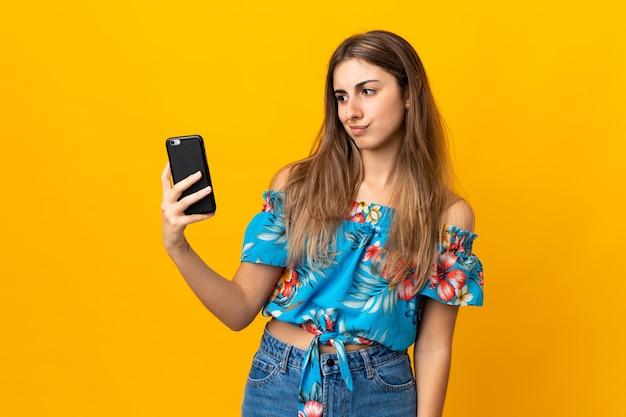 슬픈 표정으로 고립 된 노란색에 휴대 전화를 사용하는 젊은 여자