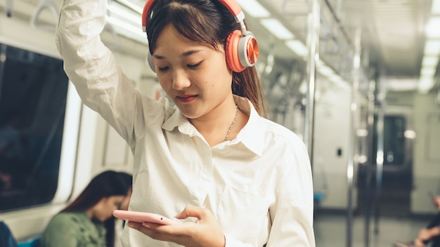 公共の電車で携帯電話を使用して若い女性