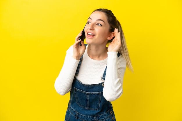 격리된 노란색 배경에서 휴대전화를 사용하는 젊은 여성이 귀에 손을 대고 무언가를 듣고 있습니다.