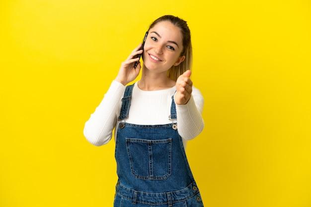Молодая женщина, использующая мобильный телефон на изолированном желтом фоне, пожимая руку для заключения хорошей сделки