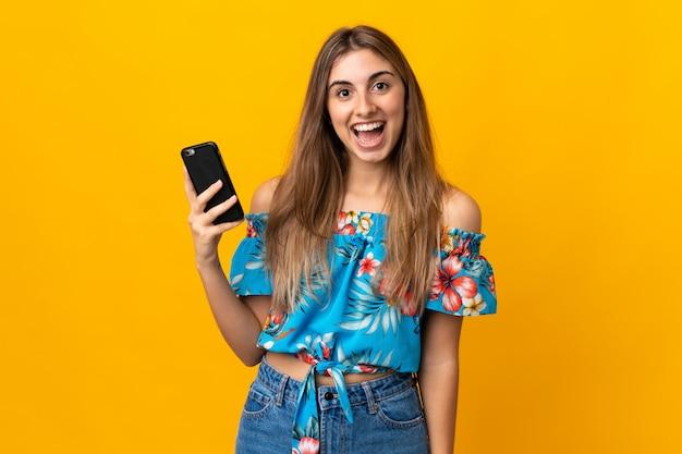 Молодая женщина, с помощью мобильного телефона через изолированную желтую стену с удивлением и шокирован выражением лица