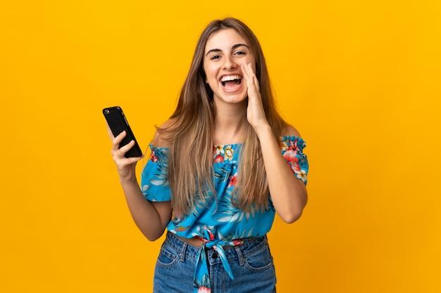 Молодая женщина, с помощью мобильного телефона на желтой стене, крича с широко открытым ртом