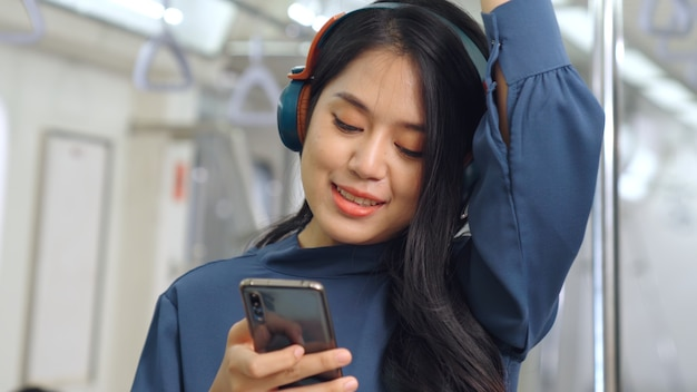 Young woman using mobile phone in public train