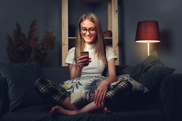 ソファに座って、携帯電話を使用して若い女性。コロナウイルスcovid-2019の期間中、家のコンセプトを維持します。閉じる。