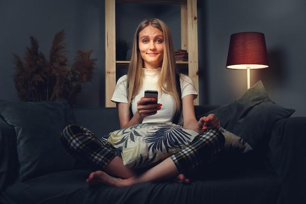 携帯電話を使用して若い女性。ソファに座っています。コロナウイルスcovid-2019の期間中、家のコンセプトを維持します。閉じる。