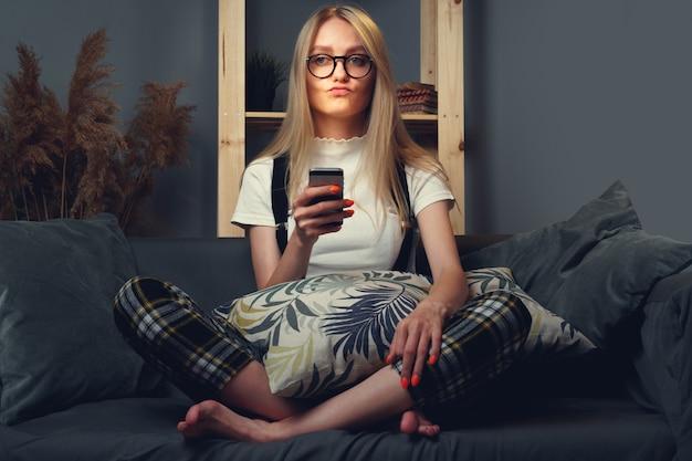 휴대 전화를 사용 하여 젊은 여자. 소파에 앉아. 코로나 바이러스 covid-2019 동안 집에 머 무르십시오.