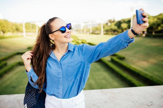 Giovane donna che utilizza il telefono cellulare prendendo selfie nel parco
