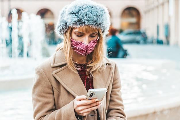 携帯電話追跡コロナウイルススプレッドを使用している若い女性-スマートフォンの携帯電話を見ているフェイスマスクを身に着けている千年紀の少女との新しい通常のライフスタイルの概念。