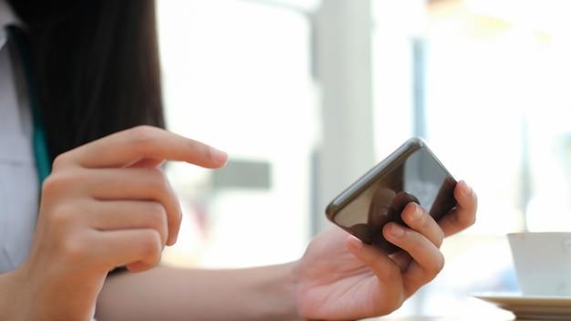携帯電話を使用している若い女性。ビジネス、教育、コミュニケーションにオンライン接続テクノロジーを使用する。