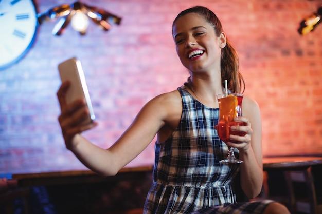 Молодая женщина с помощью мобильного телефона за коктейлем