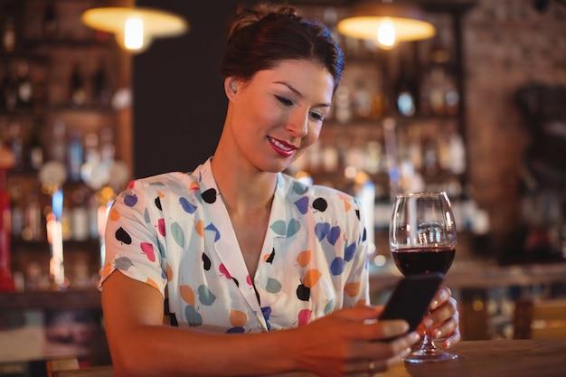 Молодая женщина с помощью мобильного телефона за бокалом вина