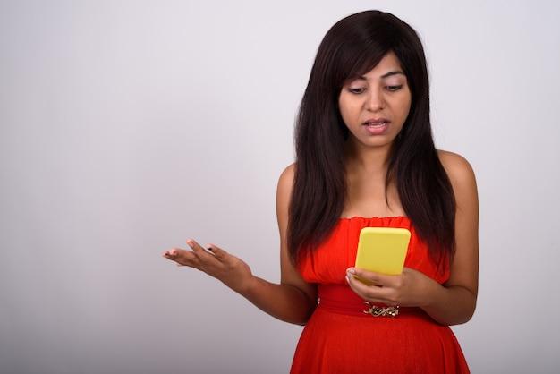 Молодая женщина, использующая мобильный телефон, выглядит смущенной и в красном платье