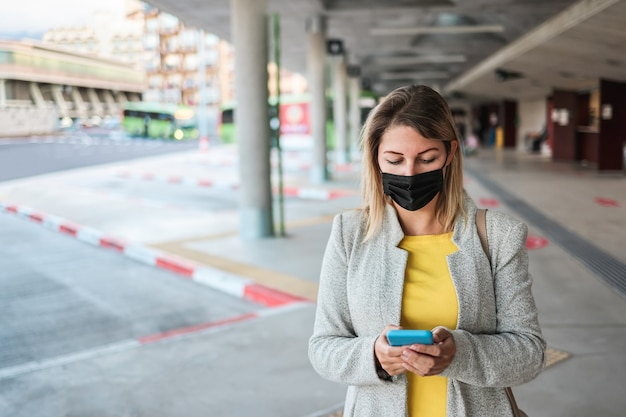 Young woman using mobile phone while waiting at bus station during coronavirus outbreak - focus on face