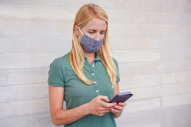 Young woman using mobile phone while wearing face mask during coronavirus outbreak