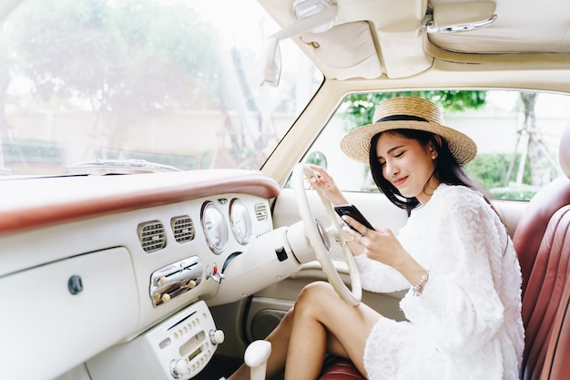 Young woman using mobile in a road trip