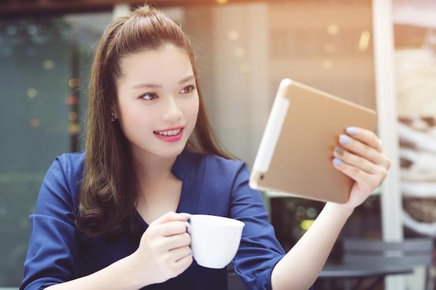 Молодая женщина с помощью мобильного смартфона в кафе