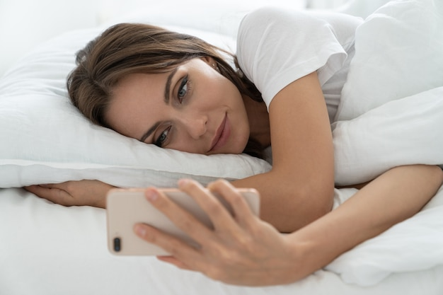 Young woman using mobile smart phone, lying and relaxing in white comfortable bed at home in morning