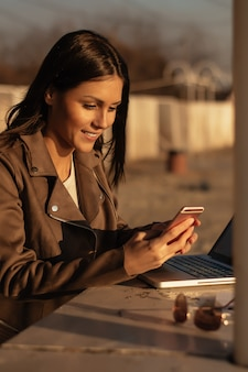 Young woman using mobile while working outdoors