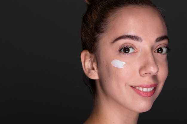 Young woman using moisturizer