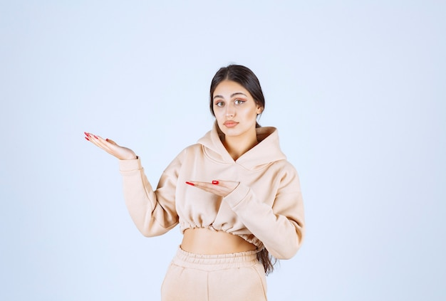 Giovane donna che utilizza le mani aperte per presentare e parlare di qualcosa