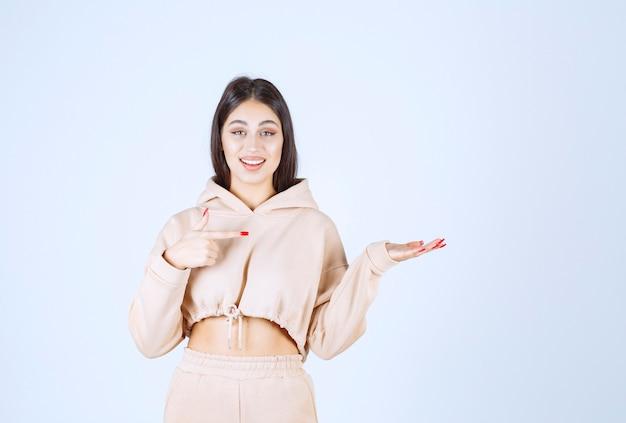 Молодая женщина, используя открытые руки, чтобы представить и поговорить о чем-то