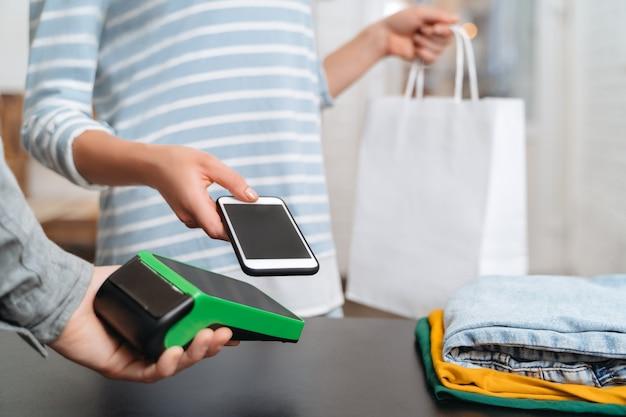 Молодая женщина, использующая платежный терминал и мобильный телефон с технологией nfc для безналичной оплаты