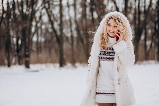 겨울 공원에서 전화를 사용 하여 젊은 여자