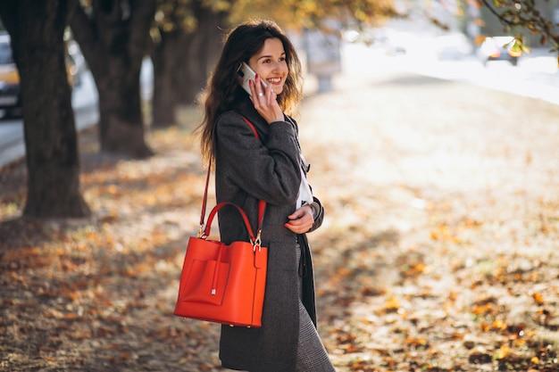 秋の公園で携帯電話を使用して若い女性