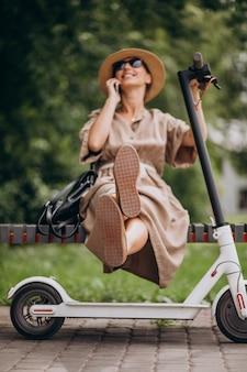 Молодая женщина, с помощью телефона в парке, сидя на скамейке на скутере