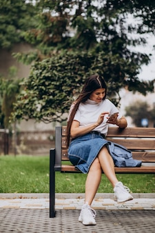 Young woman using phone and sitting on bench in park