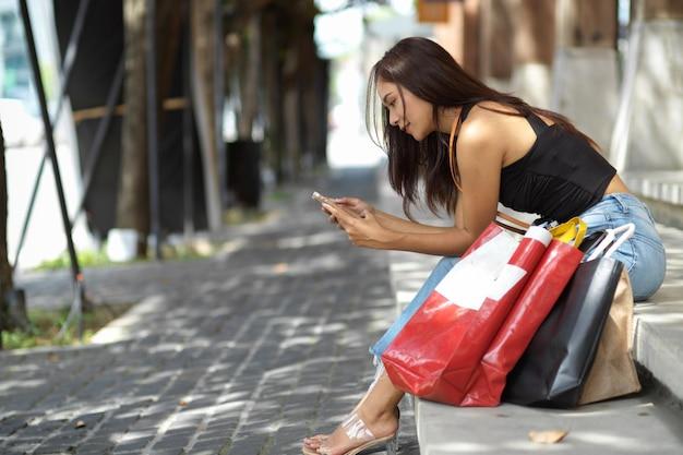 買い物後の配達車サービスを待っている店の階段に座って電話を使用して若い女性