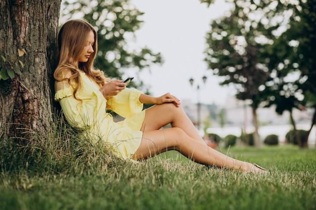 Giovane donna che utilizza il telefono e che si siede sotto l'albero nel parco