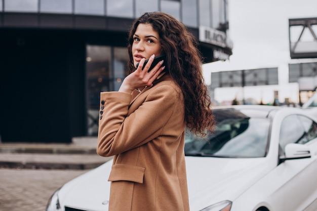 Giovane donna che usa il telefono e in piedi vicino alla macchina