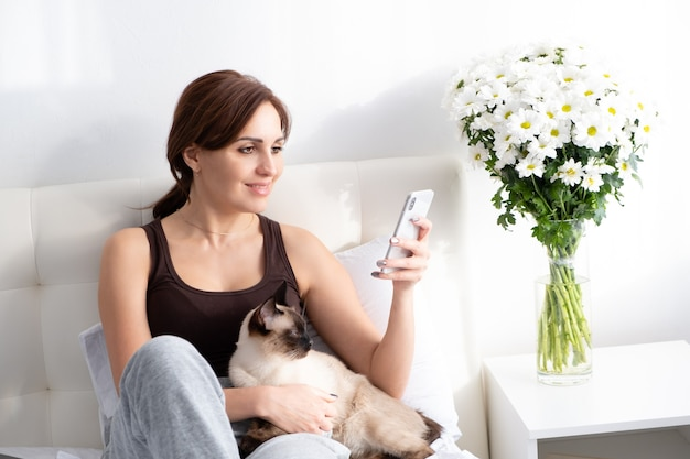Young woman using phone with her siamese cat on bedroom with flowers.