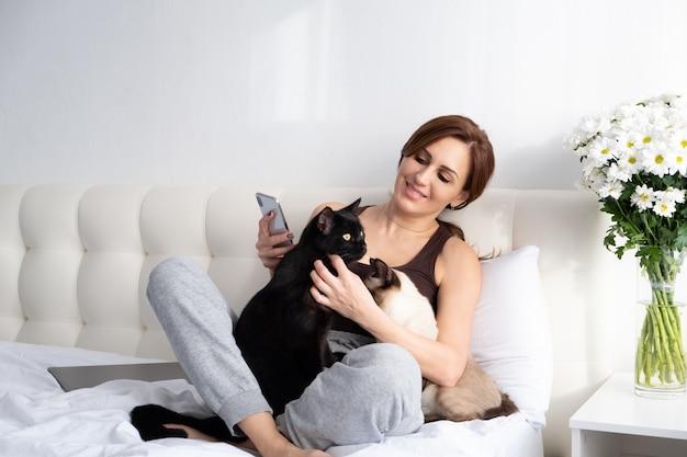 花と一緒に寝室に座っている彼女の2匹の猫と電話を使用している若い女性。