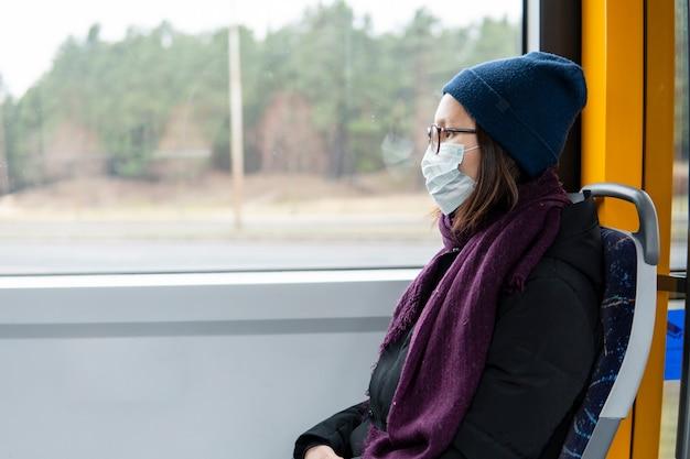 サージカルマスクと公共交通機関を使用して若い女性