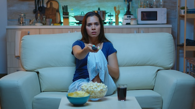 Young woman using remote controler sitting on sofa at home. excited amused alone lady in pijamas resting with snacks and juice sitting on comfortable sofa in open space living room watching tv