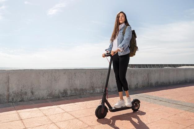 Giovane donna che utilizza uno scooter all'aperto