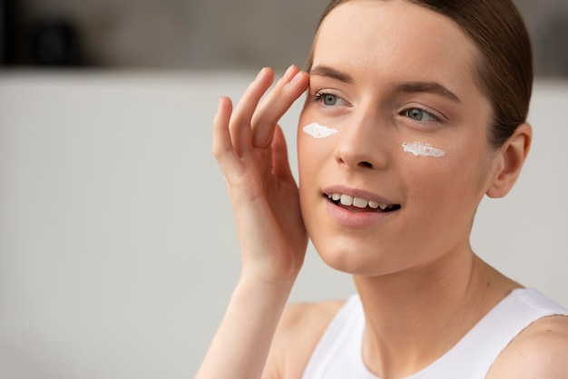 Young woman using a skin care cream