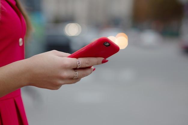 ぼやけた明るい背景で赤いケースでスマートフォンを使用して若い女性。空きスペース