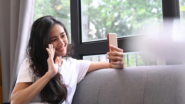 自宅のソファに座って友達とスマートフォンのビデオ通話を使用している若い女性。