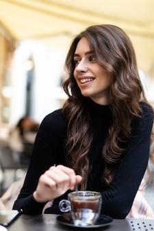 外でコーヒーを飲むスマートフォンとラップトップを使用して若い女性