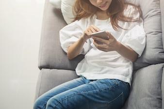 リビングルームのソファで居心地の良い家庭でスマートフォンを使用している若い女性