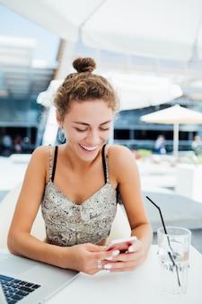 屋外のコーヒーショップでスマートフォンを使用して若い女性。