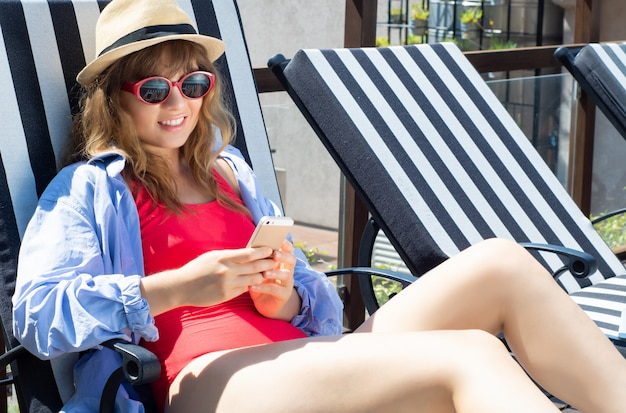 Young woman using smartphone on beach chairs.