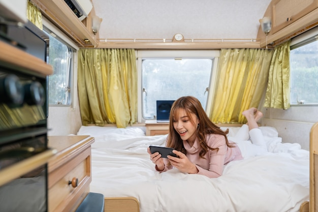 Young woman using smartphone on bed of a camper rv van motorhome