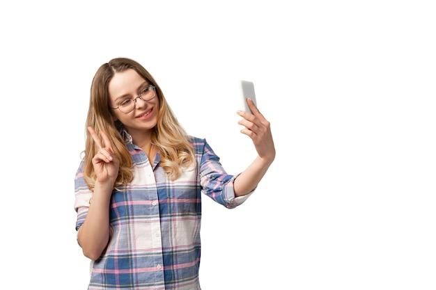 スマートフォン、デバイス、白いスタジオの壁に分離されたガジェットを使用して若い女性