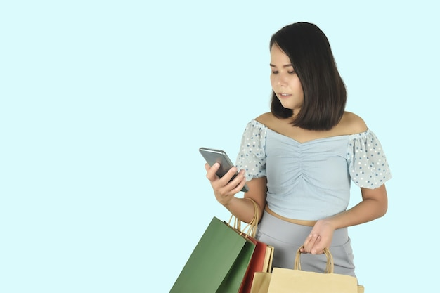 Young woman using smartphone and holding shopping bags in hands online shopping app concept