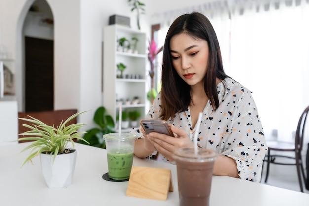 カフェでスマートフォンを使用して若い女性