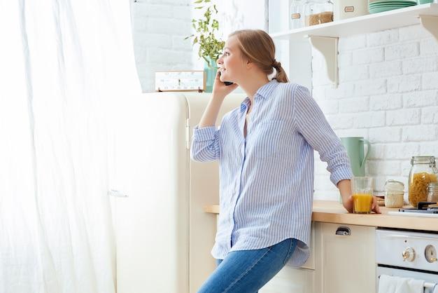 コーヒーマグカップと近代的な家の主催者と台所のテーブルにもたれてスマートフォンを使用して若い女性。